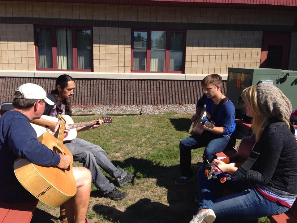 Picture of students playing guitars outside at BMCC campus